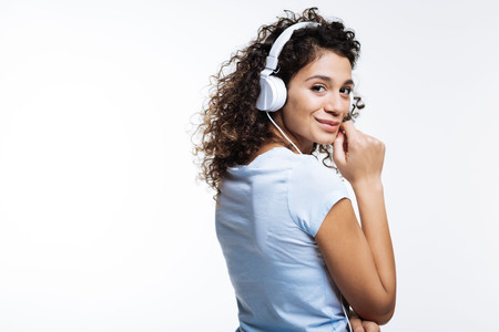 Curly-haired woman posing in headphones