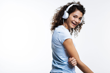 Lovely curly-haired woman listening to music and laughing Stock Photo