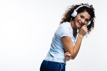 Pleasant curly-haired woman laughing while listening to music Stock Photo