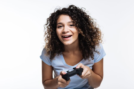 Upbeat curly-haired woman playing video games Stock Photo