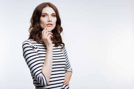 Charming woman touching her chin while posing