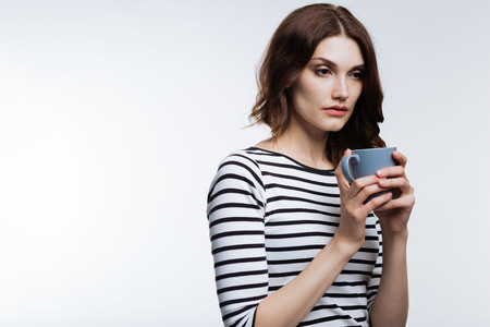 Tired auburn-haired woman drinking coffee Stock Photo