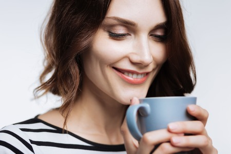 Close up of beautiful woman smelling coffee aroma Stock Photo