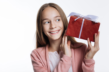 Adorable teenage girl looking at box with present Stock Photo