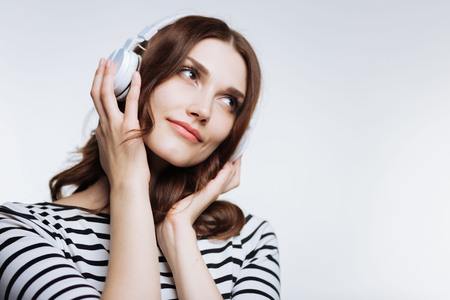 Lovely young woman listening to music in headphones