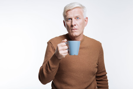 Senior man holding cup of coffee and frowning