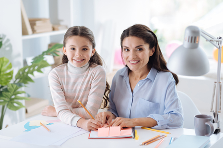 Nice cheerful mother and daughter looking at you Stock Photo