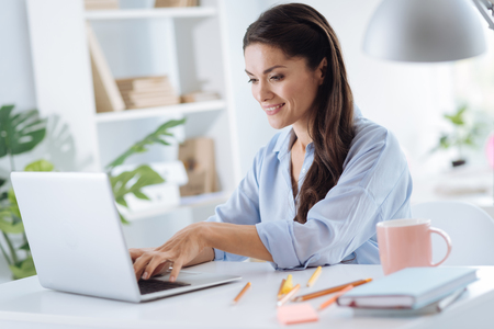 Positive attractive woman using a laptop