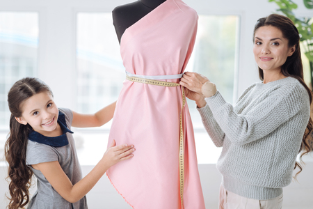 Delighted smart woman designing a dress
