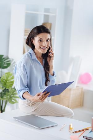 Cheerful smart businesswoman being at work