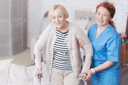 Vorsichtige Ärztin, die ihrem älteren Patienten hilft zu gehen Standard-Bild