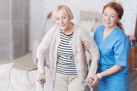Careful female doctor helping her elderly patient to walk Stockfoto