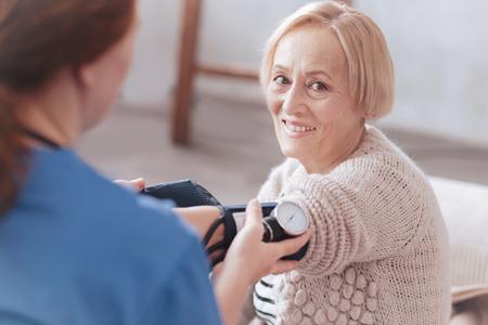bonne dame retraité sourire tout en vérifiant sa pression artérielle