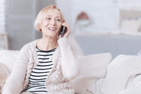 가정에서 전화로 얘기하는 빛나는 수석 아가씨 스톡 콘텐츠