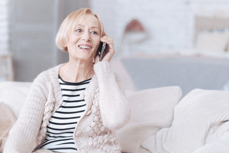 Radiant senior lady talking on phone at home