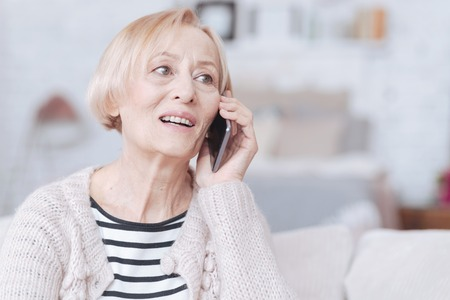 Excited retired woman having smartphone call indoors Stock Photo