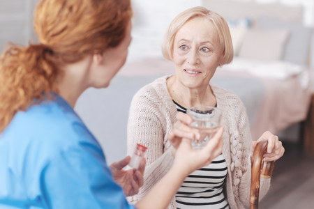 Charming senior lady looking at caregiver while taking water Stock Photo