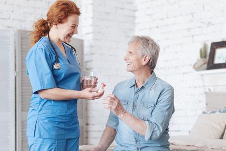 Radiant caregiver brining pills for cheerful senior man Stock Photo