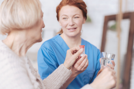 Cheerful nurse giving bottle with pill and water to patient