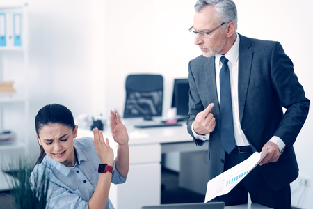 Angry mature boss shouting at stressed employee