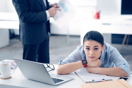 Exhausted female employee looking upset at work