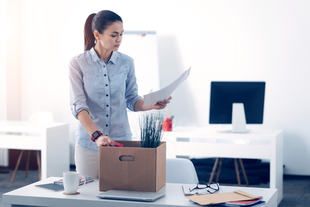Young employee packing her stuff in box while leaving work Stock Photo