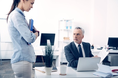 Dissatisfied box giving young female employee lecture