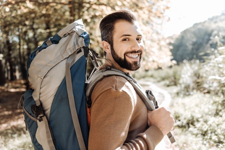 Cheerful handsome man caring a rucksack Stock Photo