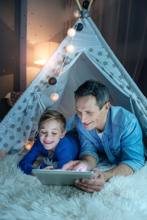 Cheerful kid looking at screen of tablet Stock Photo