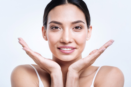 Cheerful smiling woman posing with her face between hands Stock Photo