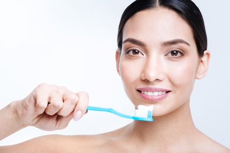Upbeat young woman brushing her teeth