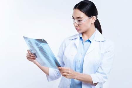 X 線検査の結果を勉強して黒髪の女性医師