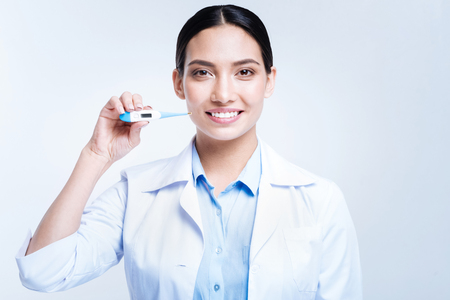 Upbeat female doctor holding thermometer and smiling