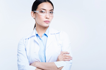 Charming lab worker in safety glasses folding her arms