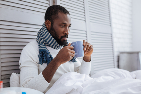 Serious man drinking warm tea at home Stock Photo