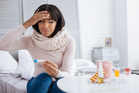 Upset woman with high temperature looking at the medicines
