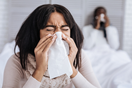constant: Unhappy woman looking tired of constant sneezing Stock Photo