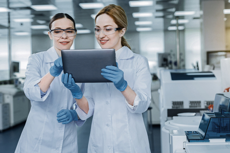 Delighted nice scientist using a tablet Stock Photo