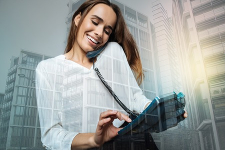 Cheerful nice woman dialing a phone number Stock Photo