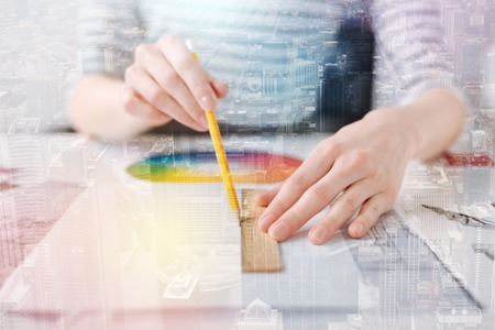 Straight line. Close up of a ruler in hands of a professional female engineer drawing a line while working on the blueprint