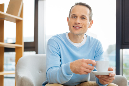 Positive mood. Nice cheerful pleasant man holing a cup of tea and smiling while looking at you