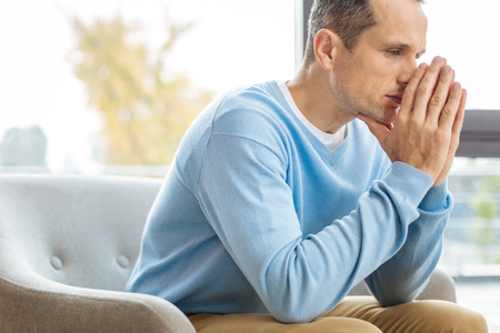 Cheerless thoughts. Unhappy gloomy adult man holding his hands together and touching his nose while having cheerless thoughts Stock Photo
