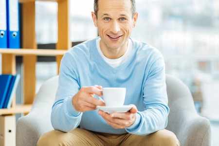 Positive emotions. Happy delighted joyful man holding a cup of coffee and smiling while being in a positive mood Stock Photo