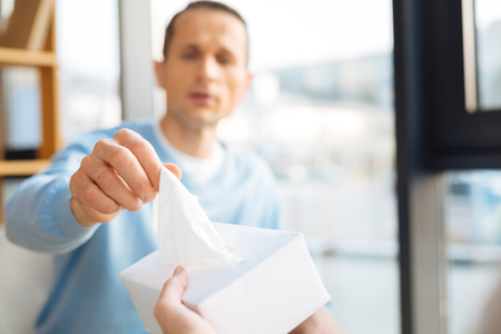 Wipe away tears. Selective focus of a paper tissue being taken out of the box by a nice pleasant handsome man
