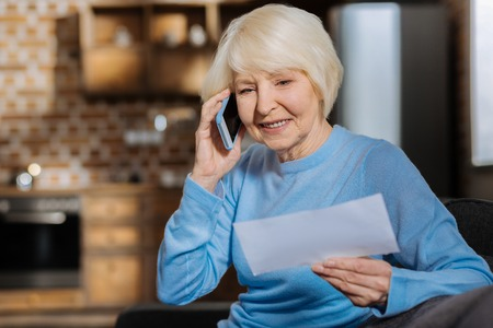Distance communication. Delighted positive elderly woman holding a bill and smiling while making a phone call