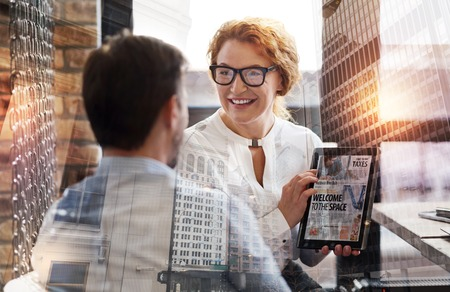 Nice report. Beautiful middle-aged woman showing the tablet with a news article to her boss and making a report about the editorial Stock Photo