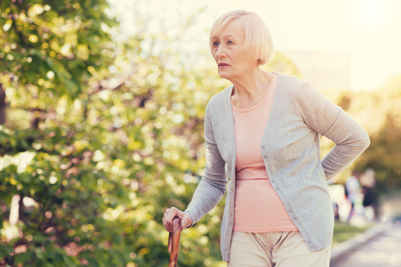Unpleasant pain. Pleasant sad elderly woman leaning on the walking stick and holding her back while feeling pain there