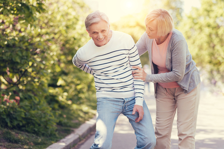 In the back. Sad unhappy elderly man standing together with his wife and feeling pain in the back while having a walk Stock Photo