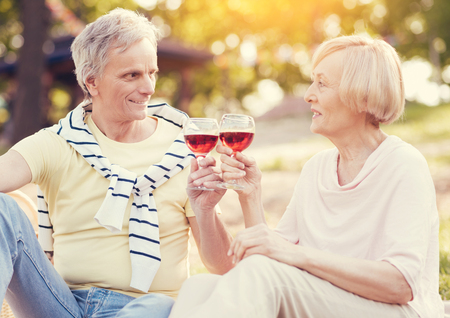 Day out. Positive nice elderly couple sitting together and drinking wine while having a picnic