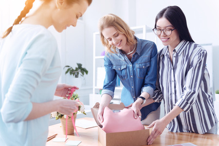 Amazing present. Joyful smiling women putting a beautiful pink dress into the box while standing near the table Stock Photo